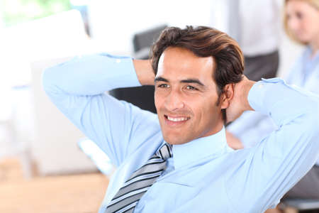 relaxed business man: Smiling relaxed businessman in office Stock Photo
