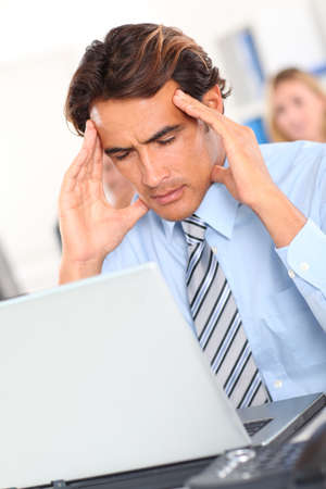 Businessman having a headache in front of laptop photo