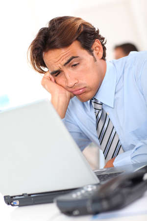 fed up: Businessman with tired look at work