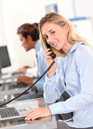 answering phone: Office worker answering the phone