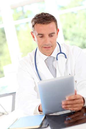 uniforme medico: Retrato de la sonrisa profesional que usa la tableta Foto de archivo