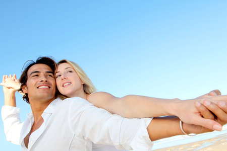 exotism: Happy couple stretching arms at the beach