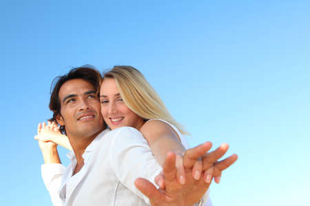 Happy couple stretching arms at the beach Stock Photo - 10626179