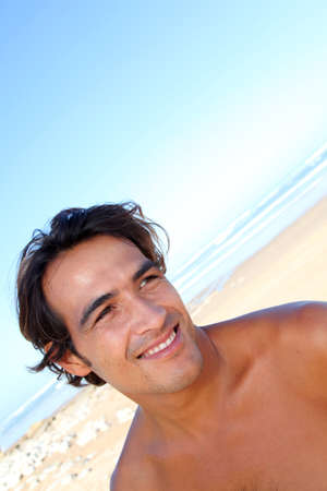 Portrait of handsome guy at the beach photo
