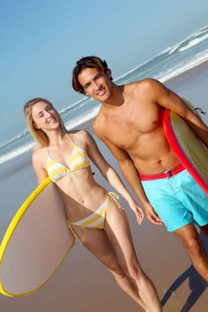 Couple at the beach with surfboard photo