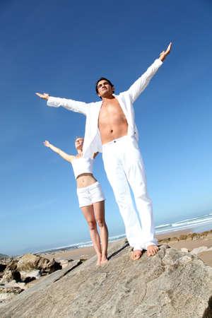 manos levantadas al cielo: Pareja haciendo ejercicios de yoga en la playa