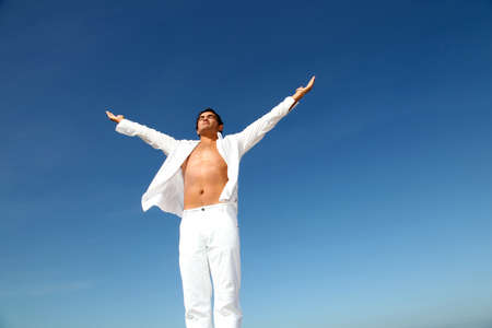 manos levantadas al cielo: Hombre haciendo ejercicios de meditaci�n en la playa Foto de archivo