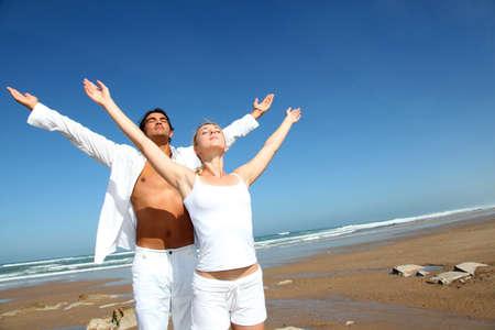 pareja saludable: Pareja haciendo ejercicios de yoga en la playa