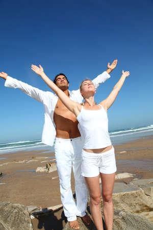 persona respirando: Pareja haciendo ejercicios de yoga en la playa
