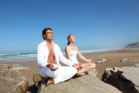 breath: Couple doing yoga exercises on the beach