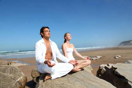 atmung: Paar macht Yoga Übungen am Strand