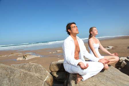 respiration: Couple � faire des exercices de yoga sur la plage