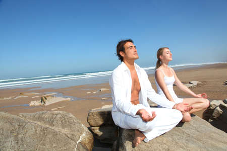 respiracion: Pareja haciendo ejercicios de yoga en la playa