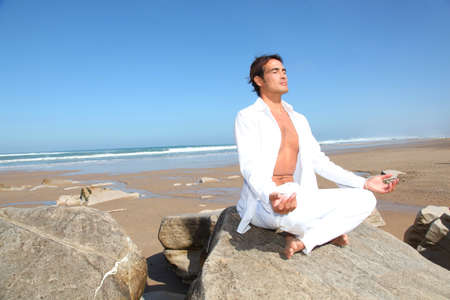 yoga rocks: Man doing meditation exercises on the beach