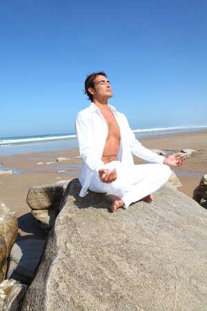 Man doing meditation exercises on the beach photo