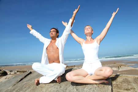 breathing exercise: Couple doing yoga exercises on the beach