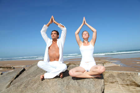 raised arms: Couple doing yoga exercises on the beach