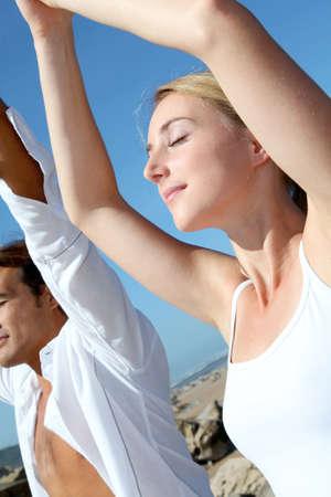 Couple doing yoga exercises on the beach photo