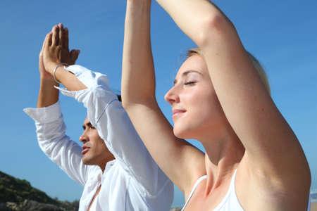 yoga rocks: Couple doing yoga exercises on the beach