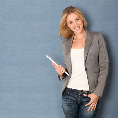 pda: Young woman standing on grey background with touchpad