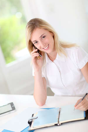 noting: Blond woman in office talking on the phone