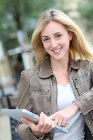 Beautiful woman using electronic tablet in public park photo