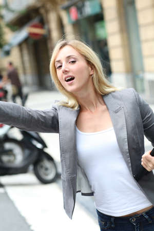 Businesswoman hailing for a cab photo