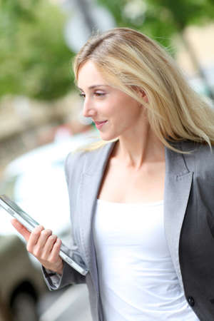 websurfing: Businesswoman holding electronic tablet in town Stock Photo