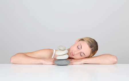 piling: Woman resting with eyes shut by pile of pebbles