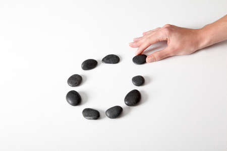 white pebble: Human hand arranging line of pebbles in circle