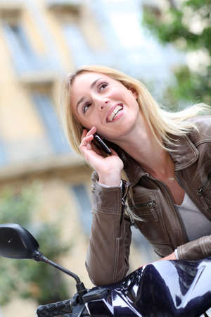 Blond girl sitting on motorcycle with telephone photo
