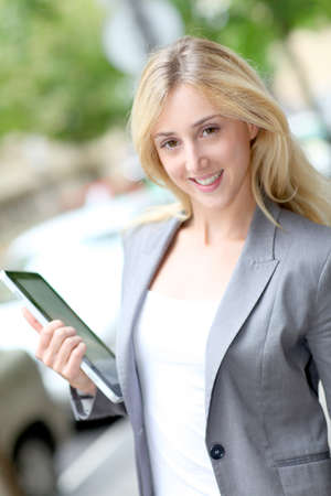 Businesswoman holding electronic tablet in town photo