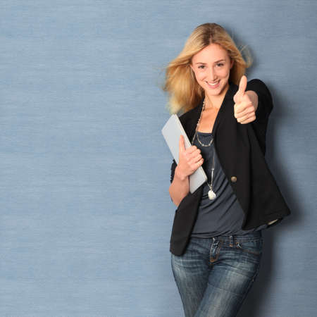 succesful: Beautiful woman leaning on wall with touchpad