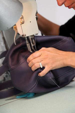 to sew: Closeup on woman sewing leather handbag