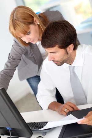 Business team in office working on desktop computer photo