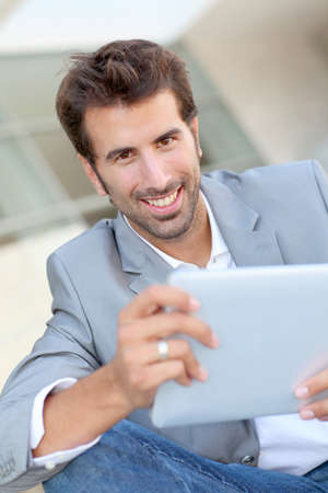 Portrait of smiling man using electronic tablet outside photo
