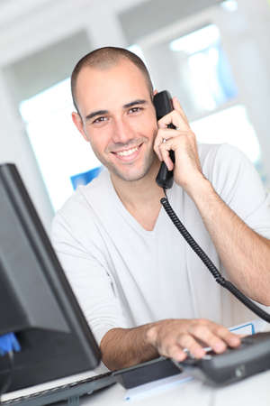 answering phone: Smiling man answering the phone