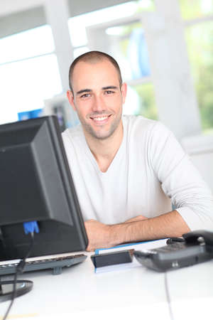 ordinateur de bureau: Employ� de bureau Sourire assis en face de l'ordinateur de bureau