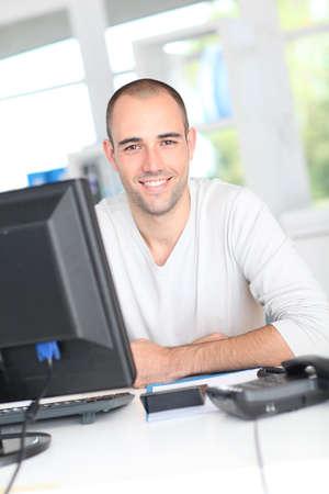desktop computer: Smiling office worker sitting in front of desktop computer