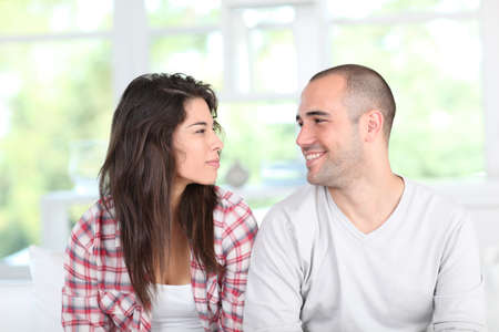 facing: Young couple at home sitting in couch
