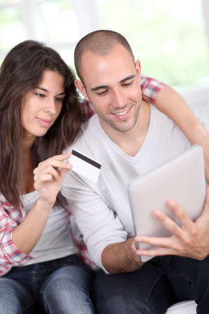 Young couple doing online shopping using electronic tablet Stock Photo - 10772498