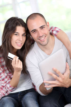 Young couple doing online shopping using electronic tablet photo