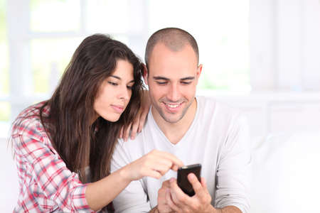 Young couple doing online shopping with smartphone photo