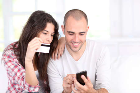 woman smartphone: Young couple doing online shopping with smartphone