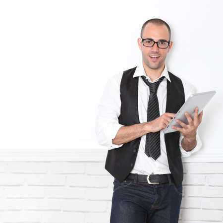 Stylish handsome guy leaning on wall with touchpad Stock Photo - 10772850