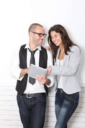 30 years old man: Trendy couple leaning on wall with electronic tablet Stock Photo