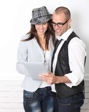 Trendy couple leaning on wall with electronic tablet photo