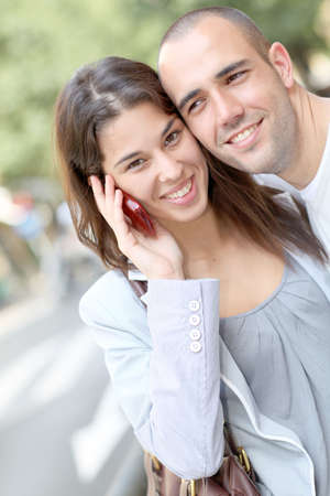 Portrait of young couple in town with smartphone photo