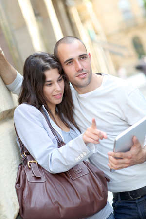 Young couple in town with electronic tablet photo