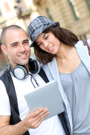 Young couple using electronic tablet in town photo